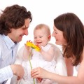 portrait-of-happy-family-with-baby-daughter-playing-with-flower